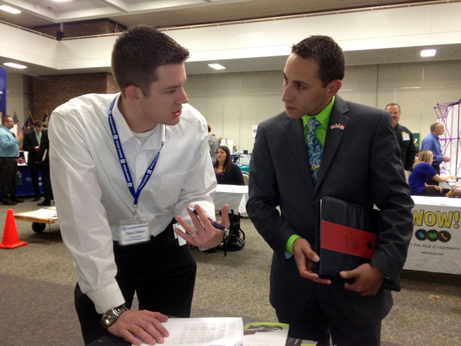 GM engineer Ryan Church (left) assists an applicant at a recent veterans' career fair in Metro Detroit. Church is a member of GM's Veterans Affinity Group and a 12-year veteran of the U.S. Air Force and Air National Guard.